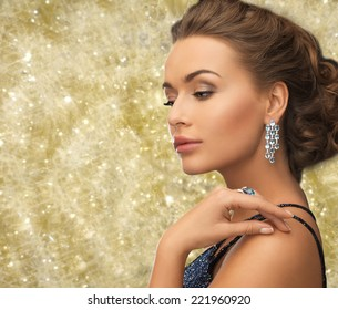 people, holidays and glamour concept - beautiful woman in evening dress wearing ring and earrings over yellow lights background