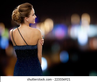 people, holidays and glamour concept - smiling woman in evening dress over night lights background