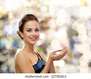 people, holidays and glamour concept - smiling woman in evening dress with diamond over lights background