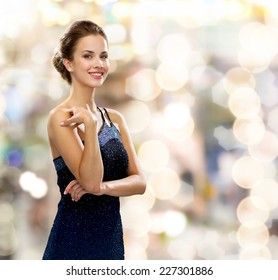 people, holidays and glamour concept - smiling woman in evening dress over lights background