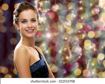 people, holidays, jewelry and glamour concept - happy beautiful woman wearing pearl earrings over christmas lights background