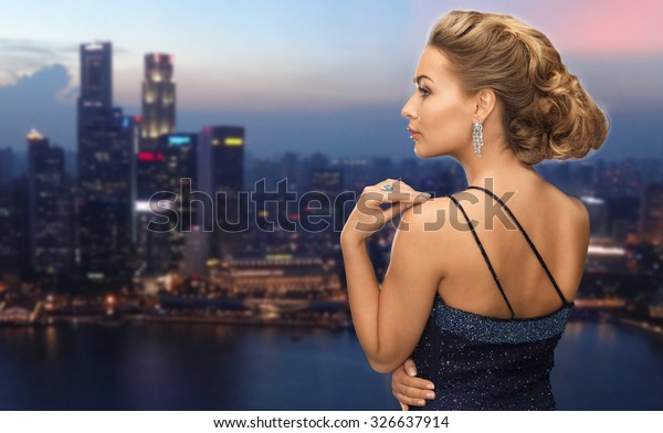 people, holidays, jewelry and glamour concept - beautiful woman with diamond earring over night singapore city background
