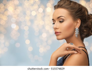 people, holidays, jewelry and luxury concept - woman in evening dress with diamond earring over lights background