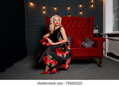 people, holidays, jewelry and luxury concept - Beautiful brunette, elegant woman portrait. Retro lady with red lips makeup, wavy hairstyle, fashion gems jewelry posing modern bed in interior
