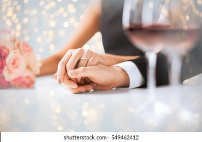 people, holidays, proposal, engagement and wedding concept - close up of engaged couple holding hands over lights background