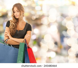 people, holidays and sale concept - young woman with shopping bags over lights background