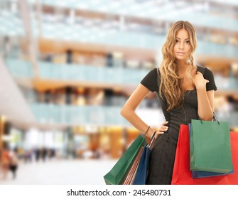 people, holidays and sale concept - young happy woman with shopping bags over mall background