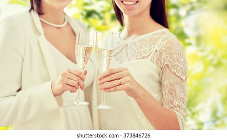 people, homosexuality, same-sex marriage, celebration and love concept - close up of happy married lesbian couple holding and clinking champagne glasses over green background