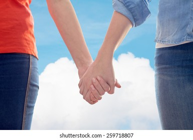 people, homosexuality, same-sex marriage, gay and love concept - close up of happy lesbian couple holding hands over blue sky and cloud background