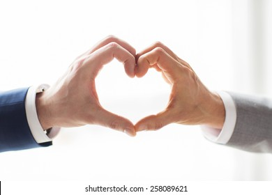 people, homosexuality, same-sex marriage, gesture and love concept - close up of happy male gay couple hands showing heart hand sign