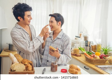 People, homosexuality, same-sex marriage and love concept..Happy male gay couple cooking together and Woke up to make breakfast and tease together at kitchen.
