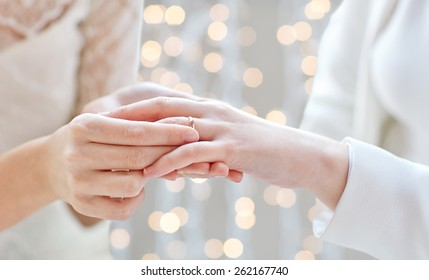 people, homosexuality, same-sex marriage and love concept - close up of happy lesbian couple hands putting on wedding ring over holidays lights background