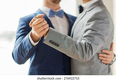 people, homosexuality, same-sex marriage and love concept - close up of happy male gay couple holding hands and dancing on wedding