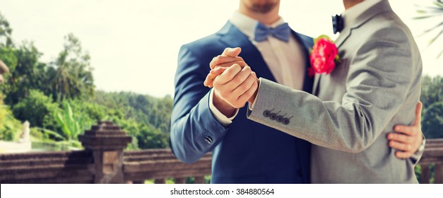 people, homosexuality, same-sex marriage and love concept - close up of happy male gay couple holding hands and dancing on wedding over balcony and nature background