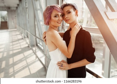 people, homosexuality, same-sex marriage, travel and gay love concept - close up of happy women couple hugging over metall bridge. Two girlfriend walking
