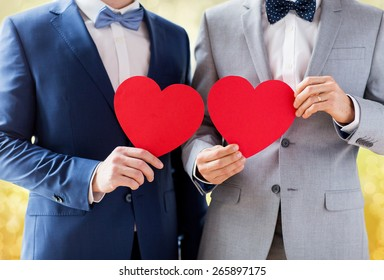 people, homosexuality, same-sex marriage, valentines day and love concept - close up of happy married male gay couple holding red paper heart shapes on wedding over yellow lights background