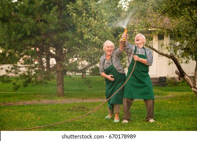 People with hose having fun. Cheerful senior couple in garden. Make it rain.