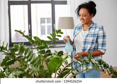 people, housework and care concept - happy african american woman or housewife spraying houseplant with water sprayer at home