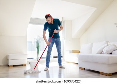 people, housework and housekeeping concept - happy man in headphones with mop cleaning floor at home
