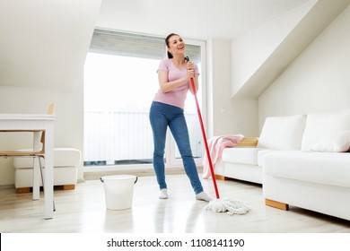 people, housework and housekeeping concept - happy woman or housewife with mop cleaning floor and singing at home