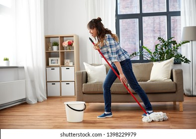 people, housework and housekeeping concept - happy asian woman with mop and bucket cleaning floor and having fun at home