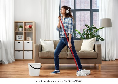 people, housework and housekeeping concept - happy asian woman in headphones with mop and bucket cleaning floor and singing at home