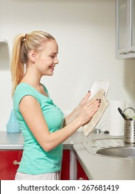 people, housework and housekeeping concept - happy woman wiping dishes at home kitchen