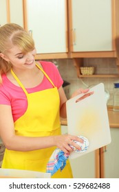 People, housework and housekeeping concept. Woman doing the tidying up in kitchen cleaning plastic cutting board with rag sponge