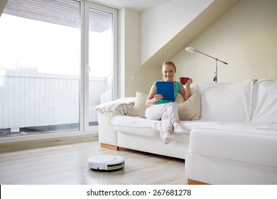 people, housework and technology concept - happy woman with tablet pc computer and robot vacuum cleaner drinking tea at home