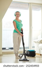 people, housework, technology and housekeeping concept - happy woman in headphones with vacuum cleaner cleaning floor at home