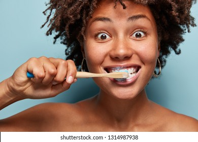 People and hygiene concept. Headshot of dark skinned woman with crisp hair, brushes and whitens teeth, cares for dental health, isolated over blue background, has morning routine. Stomatology concept