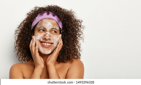 People, hygiene and pampering concept. Happy Afro American woman has curly hairstyle, washes face with soap, cleans skin, has refreshing procedures, stands shirtless against white background