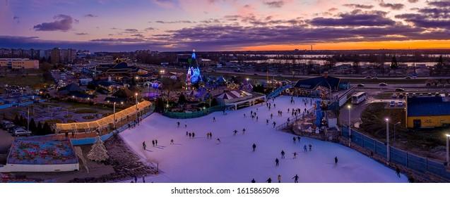 People ice skating near the beautiful Christmas tree at dusk during purple sunset. Beautiful Christmas spirit.