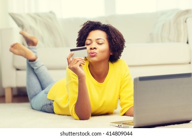 people, internet bank, online shopping, technology and e-money concept - happy african american young woman lying on floor with laptop computer and credit card at home