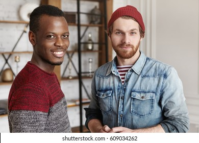 People and interracial friendship concept. Two old male friends that came across each other at cafe standing in modern cafe interior and having conversation, both looking at camera with happy smiles