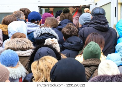 People  in  jackets crowd near the store entrance during the sale. Shoppers enter the mall on Black Friday, winter sale, discounts
