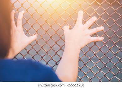 people in jail. hand at the cage.