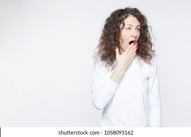 People, job, career and overwork concept. Tired young Australian woman employee covering opened mouth with hand while yawning at end of working day in office, feeling sleepy and bored. Body language.