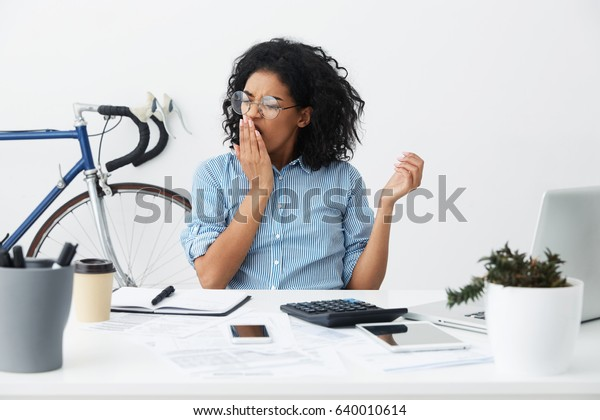 People, job, career and overwork concept. Tired young dark-skinned woman employee in eyewear covering opened mouth with hand while yawning at the end of working day in office, feeling sleepy and bored