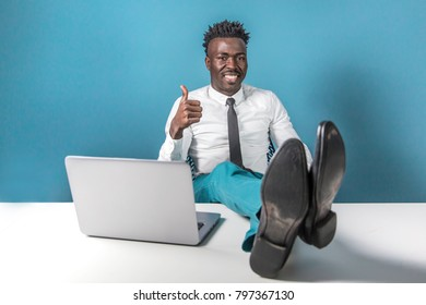 People, job, occupation, profession and career concept. Portrait of experienced skilled dark-skinned male model on a blue background, relaxing on a chair, smiling and giving a thumbs up.