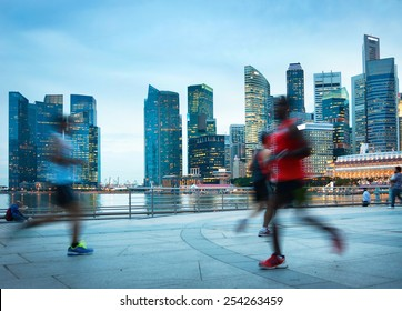 People jogging at dusk in Singapore. Singapore Downtown Core in the background