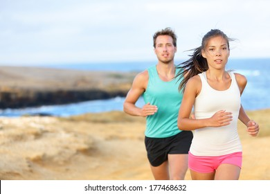 People jogging for fitness running in beautiful landscape nature outdoors. Woman and man sports athletes training cross-country trail running. Couple together, Asian woman, Caucasian man,