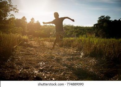 The people joy of a country boy local in thailand with nature Boy jumping on sunset background