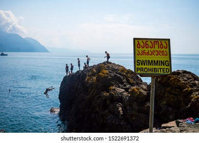 People jump from a cliff into the sea in a forbidden place, Georgia, Batumi August 15, 2019