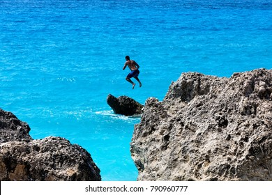 People to jump playing in the sea at the Kavalikefta Beach in Lefkada Island, Greece