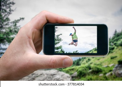 People jumping for joy, jump height. photos from your phone, Self, photographing on the phone, the man photographs the mountain landscape on the phone (smartphone) side view