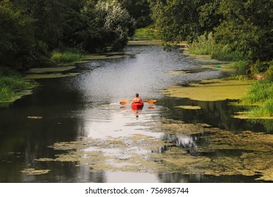 People kayaking on river with duckweed. Canoeing with friends. Man with kayak and oars. Bushes and trees on the shore. Scenic serene landscape with water. Relaxing recreation sport. People having fun.