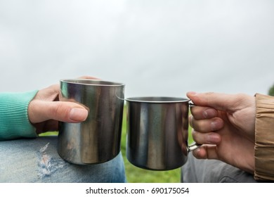 People keep two tourist mugs on picnic by day