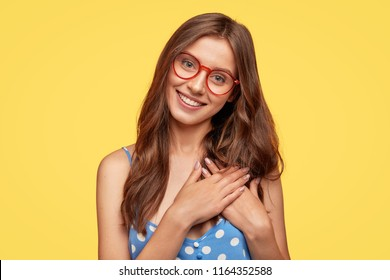 People, kindness and generosity concept. Cheerful young comely woman in spectacles keeps hands on heart, expresses cordialty and friendliness, has charming smile, poses against yellow studio wall