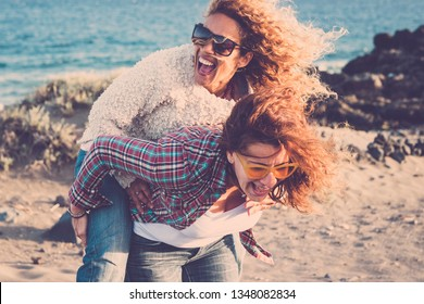 People laughing a lot and have fun together in friendship in outdoor leisure activity - couple of women gone crazy carrying eachother on the shoulder - no limit age to be playful and happy